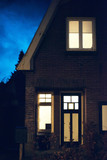 Illuminated windows and front door of house at dusk. - 248156521