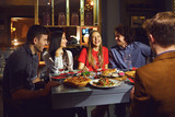 A group of friends eating at a dinner in a restaurant. - 248158531
