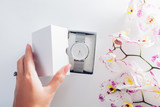 Woman opens a gift box with silver hand watch surrounded with orchid. Present for Valentine's day
