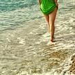 beautiful young relaxing woman walking barefoot on beach on the sea. legs closeup