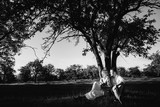 A beautiful couple is resting outside the city, sitting near a big tree in the garden and smiling. Black and white photo