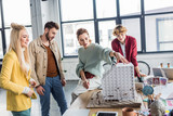 group of female and male architects working together on house model in loft office