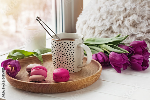 Leinwandbild Motiv A cup of tea, sweet dessert macarons and purple tulips on a window sill.