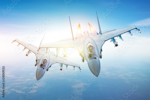 fototapeta na ścianę Pair of combat fighters, in conjunction flying in the sky over the territory.