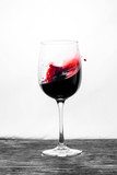 Red wine in the glass splashes in action on a white background. Stylish design card - 248176187
