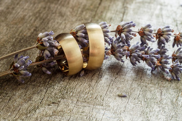 Wedding rings and lavender flower on wooden background