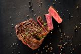 Restaurant cooking art. Grilled steak sliced on textured black background. - 248197573