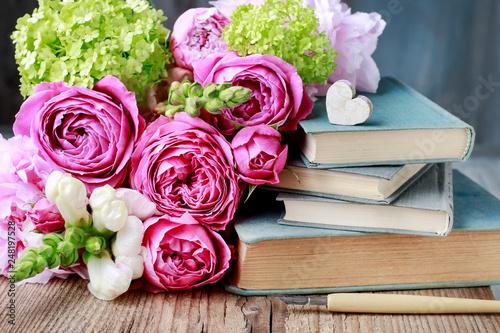 Leinwandbild Motiv Old books and bouquet of flowers.