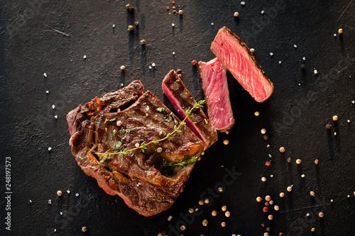Leinwanddruck Bild Restaurant cooking art. Grilled steak sliced on textured black background.