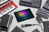 Playing song on tablet with electronic music instruments around