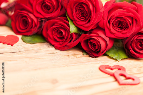 Rote Rosen Blumenstrauß mit Herzen auf Holz Tisch - 248202598