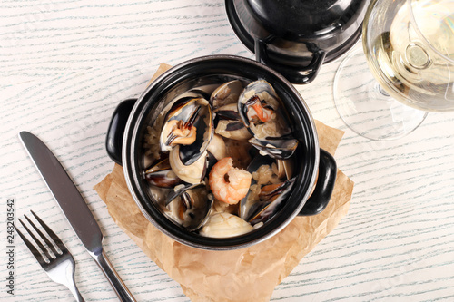 Shell and shrimp in small pan on white wood  - 248203542