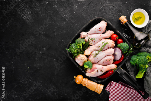 Raw chicken legs and spices and herbs. Barbecue. On a black stone background. Top view. Free copy space.