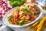 Italian pasta spaghetti bolognese in white bowl with tomatoes parmesan cheese and basil - 248214322