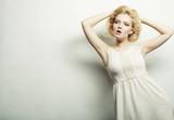 young fashion woman in white dress posing in studio
