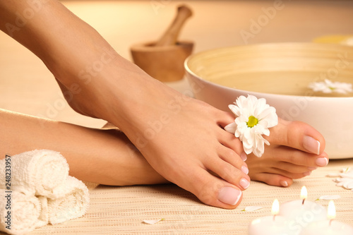 Leinwandbild Motiv The picture of ideal done manicure and pedicure. Female hands and legs in the spa spot.