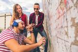 Three friends looking graffiti on the wall