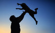 Leinwandbild Motiv Loving father and his little son having fan together outdoors. Family as silhouette on sunset.