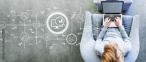 Leinwandbild Motiv Stock trading concept with man using a laptop in a modern gray chair