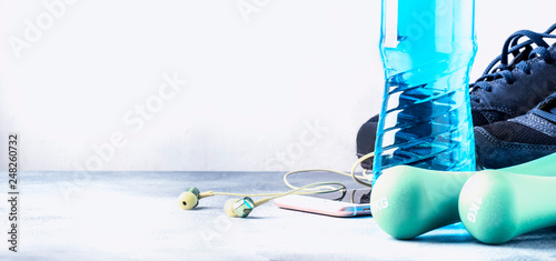 Female fitness concept: light dumbbells, isotonic blue water, smartphone with headphones and running shoes on gray concrete floor, selective focus