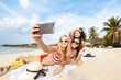 Beautiful happy girlfriends having fun on the beach taking selfies during vacation and travel