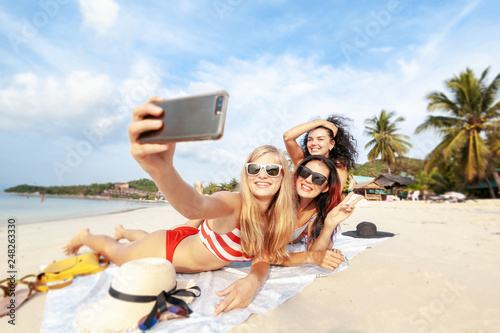 Foto Murales Beautiful happy girlfriends having fun on the beach taking selfies during vacation and travel