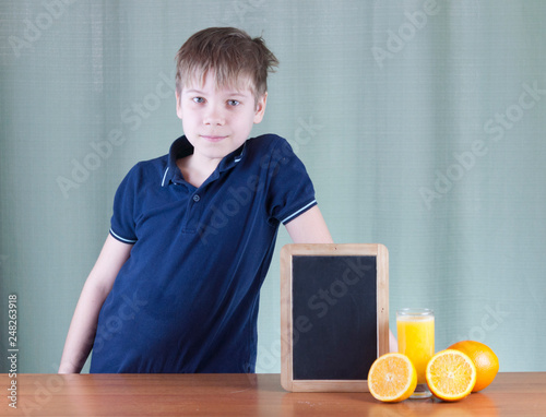 Cute little boy and glass of orange juice at table, on background