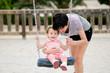 Leinwandbild Motiv Mother swinging her little daughter on a swing