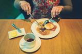 Young woman having breakfast in hotel