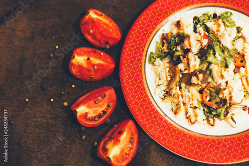 Salad on the plate with tomatoes on the dark background. - 248284737