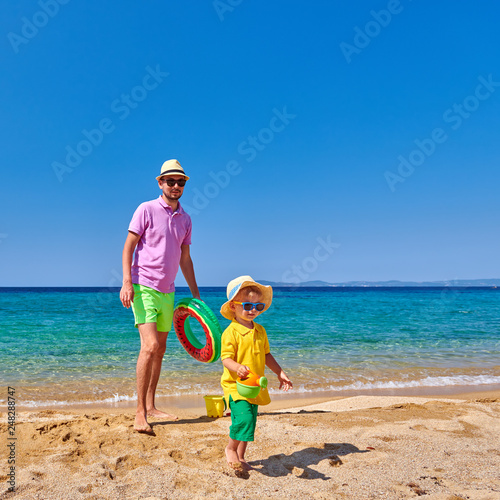 Leinwandbild Motiv Toddler boy walking on beach with father