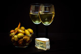 Large pickled green olives in a bowl and white wine in a glass and blue cheese over black background - 248295349