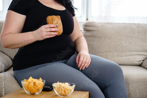 Leinwandbild Motiv lack of physical activity, imbalanced nutrition, laziness, homebody. lonely fat woman watching series at tv eats junk food