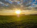Sunset on the cloudy sky over a green field, mountains in the back - 248306369