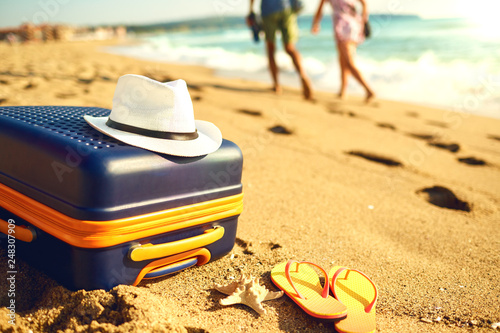 Foto Murales Suitcase and hat on the sand of the sea beach.