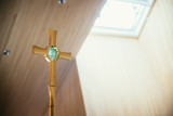 Golden metal crucifix in the church, incidence of light in the blurry background