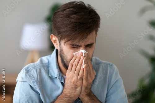 Leinwanddruck Bild Sick man got flu allergy sneezing in handkerchief blowing nose