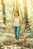 Caucasian dreamy young woman is hiking in the forest, autumn - 248315104