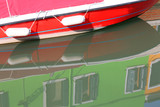 reflection of the red boat in the waterway and the houses of gre - 248329103