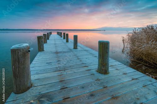 Sonnenaufgang am See mit Steg im Winter © kentauros