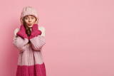Studio portrait of young lovely woman has folded lips, makes grimace at camera wears knitted hat and loose pink jumper, isolated over rosy background with empty space for your promotion or slogan - 248350524