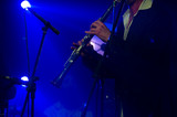 Artist, musician performing jazz with clarinet in the blue light, scene, performance concept
