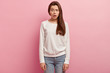 Studio shot of puzzled human raises eyebrows, has scared facial expression, dressed in white sweatshirt and jeans, isolated over rosy background. Pretty woman expresses disbelief, opens mouth