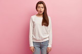 Studio shot of puzzled human raises eyebrows, has scared facial expression, dressed in white sweatshirt and jeans, isolated over rosy background. Pretty woman expresses disbelief, opens mouth - 248352538