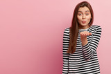 Indoor shot of pleasant looking young woman has extended hand near mouth, keeps lips folded, dressed in striped sweater, shows air kiss, isolated over rosy background, empty space for your text - 248352598