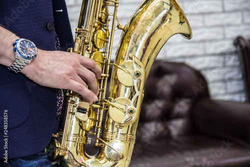 men's hands holding a saxophone against a white wall and a leather sofa - 248358576