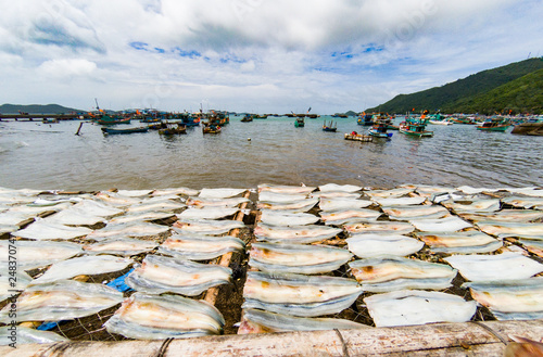 fish drying in the sun in Nam Du island, fishing boats in the background, Vietnam - 248370747