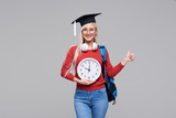 Portrait of young excited blond woman student in graduate cap with backpack holding big alarm clock isolated on grey background. Education in college. Copy space for text