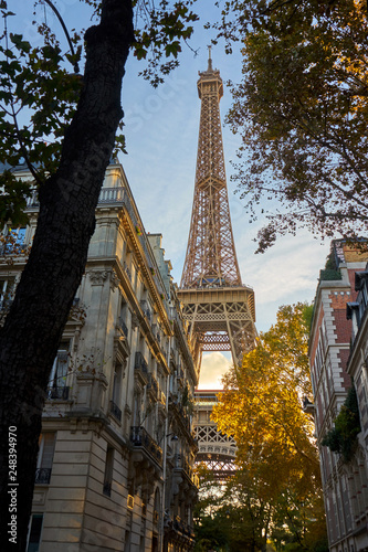 Eiffel Tower Shot Between Typical Parisian Style Buldings And Tr