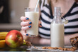 Woman drinking organic almond milk holding a glass in her hand in the kitchen. Diet vegetarian product